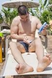 Young  man applying sun-protection cream Stock Photography