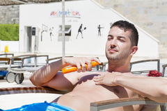 Young  man applying sun-protection cream Stock Photo