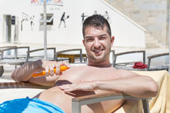 Young  man applying sun-protection cream Stock Images