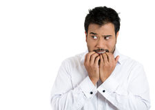 A young man apprehensive about something, afraid and anxiously biting his finger nails Royalty Free Stock Photography