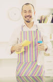 Young man in apron cleaning table Stock Photography