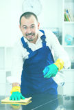Young man in apron cleaning table Royalty Free Stock Image