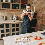 Young man cooking homemade pizza royalty free stock photography