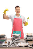 Young man with apron flexing his bicep and holding brush Royalty Free Stock Images