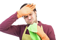 Young man with apron and gloves tired to clean. Over white background Royalty Free Stock Photos