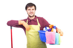 Young man with apron holding cleaning equipment Stock Photos