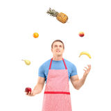 Young man in apron juggling with fruits Stock Photo