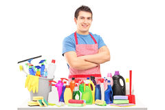 Young man in apron posing with cleaning supplies. Isolated on white background royalty free stock photo