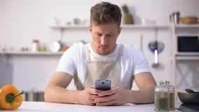 Young man in apron searching food recipe in cell phone, tips in culinary blogs. Stock footage stock video footage