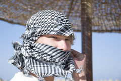 Young man with arab scarf in face. Young caucasian man with arab scarf around his face. It should safe his face for sandstorm in desert Royalty Free Stock Photo