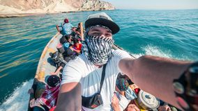Young man in the arabic scarf taking selfie from boat in the sea. Hormuz island, Iran Stock Image