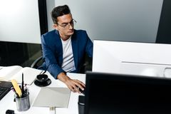 Young man architect in glasses dressed in a business suit sits at a desk in front of a computer in the office.  royalty free stock photo