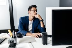 Young man architect in glasses dressed in a business suit sits at a desk in front of a computer in the office stock image
