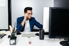 Young man architect in glasses dressed in a business suit sits at a desk in front of a computer in the office royalty free stock image