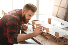 Young man architect working in the office ocuupation. Young male architect working indoors model construction royalty free stock photo