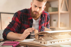 Young man architect working in the office ocuupation. Young male architect working indoors model construction royalty free stock photography