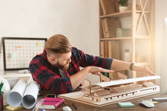 Young man architect working in the office ocuupation. Young male architect working indoors model construction stock photo