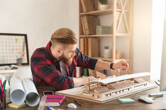 Young man architect working in the office ocuupation. Young male architect working indoors model construction royalty free stock photos