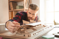 Young man architect working in the office ocuupation. Young male architect working indoors model construction royalty free stock image