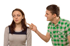 Young man arguing with his girlfriend. Young men arguing with his girlfriend pointing his finger at her as she turns aside in indifference, isolated on white Stock Images