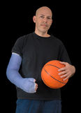 Young man in an arm cast after a basketball accident Royalty Free Stock Image