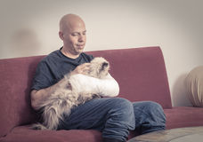 Young man with an arm cast petting his cat. Young man with an arm and elbow in a white plaster / fiberglass cast at home, relaxing while petting his cat after royalty free stock photos