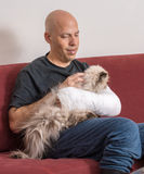 Young man with an arm cast petting his cat. Young man with an arm and elbow in a white plaster / fiberglass cast at home, relaxing while petting his cat after stock photo