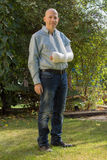 Young man with an arm cast standing in the garden Royalty Free Stock Image