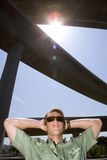 Young man with arms behind head beneath overpass, low angle view (lens flare) Royalty Free Stock Images