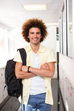 Young man with arms crossed in office corridor Stock Photo