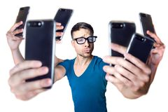 Influencer holding an exaggerated number of smartphones - isolated on white. Young man with 6 arms is holding 6 smartphones to take a selfie. Isolated on a white stock photography