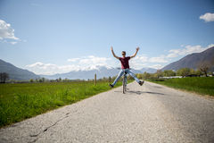 Young man arms outstreched on bicycle Stock Photo