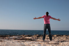 Young man with arms outstretch. Young man with arms wide open affirmating the sea Royalty Free Stock Photography