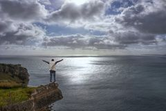 Young man on cliff`s edge, Cloudy and gloomy seascape royalty free stock photography