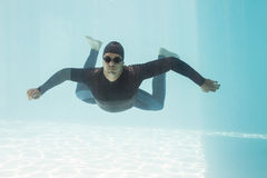 Young man with arms outstretched while swimming. Underwater Royalty Free Stock Photography