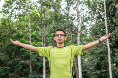 Young man arms raised enjoying the fresh air in green forest. Royalty Free Stock Photography