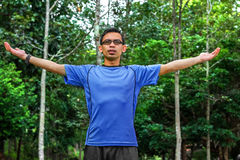 Young man arms raised enjoying the fresh air in green forest. Enjoying the nature. Young man arms raised enjoying the fresh air in green forest Royalty Free Stock Photo
