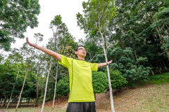 Young man arms raised enjoying the fresh air in green forest. Royalty Free Stock Photos