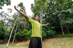 Young man arms raised enjoying the fresh air in green forest. Enjoying the nature. Young man arms raised enjoying the fresh air in green forest Stock Photo