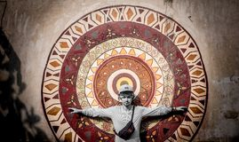 Young man with arms raised with mandala picture on the background. royalty free stock photography