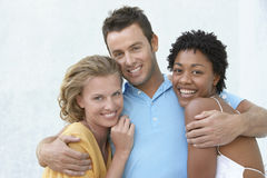 Young Man With Arms Round Two Female Friends Royalty Free Stock Photos