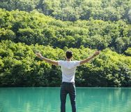 Young man, arms spread open enjoying freedom in. Young man in t-shirt, outdoor with arms spread open enjoying freedom in front of lake, seen from the back Royalty Free Stock Images