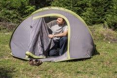 Young man arranging the tent door Stock Photography