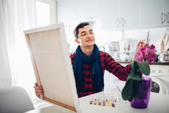 Young man artist painting at home creative painting.  royalty free stock image