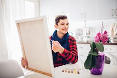 Young man artist painting at home creative painting stock photos