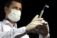 Young man as a doctor gives a medical injection to Cuban flag on a black background Stock Image