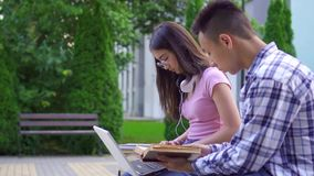 Young male asian student with book and young asian woman with laptop in park slow mo stock video