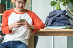 Young man asian teenager using mobile phone chatting with friend. S after class at university campus,Education concept Stock Photo