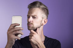 Young man asking himself. Young man looking doubtful to his mobile phone Stock Photos