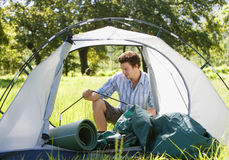 Young man assembling dome tent on camping trip in woodland clearing royalty free stock photos